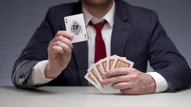 Muž drží hrací karty v ruce a ukazovat karty eso. Hazardní karetní hra