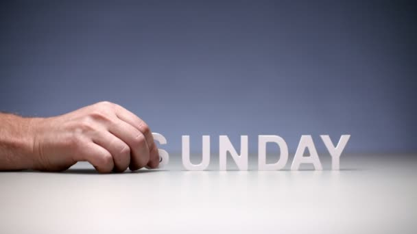 Male hand composition word sunday on table background. Day in week for rest