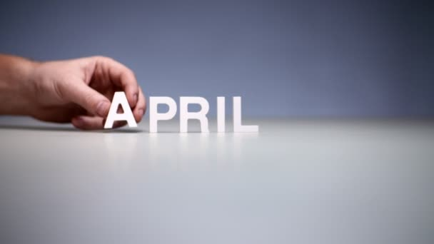 Male hand composition word april. Spring months on calendar and seasons in year