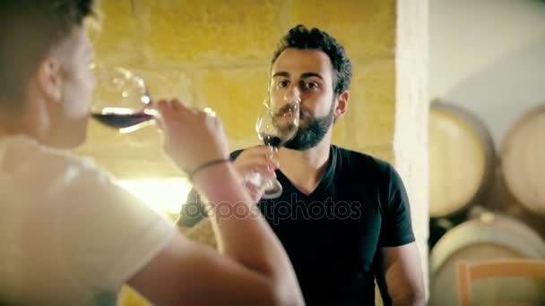 Muž vinaře a sommeliera ochutnávka červeného vína na sklep na sudy pozadí
