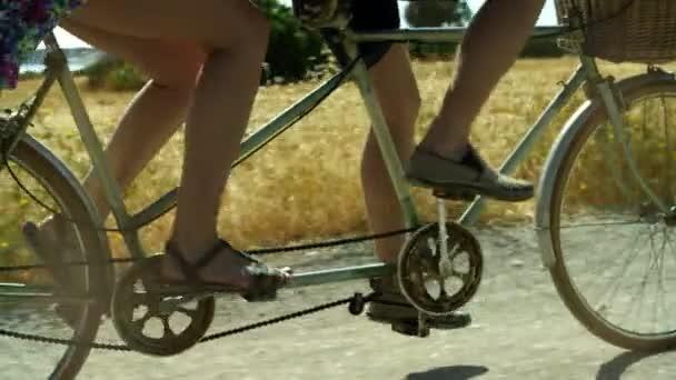 Utazás pár férfi és a nő lovagolni a kerékpár tandem road-on múlt nyáron mező