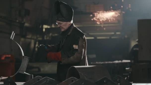 Tovární zaměstnance v ochranné masky svařování kovových detailů na jiskry pozadí