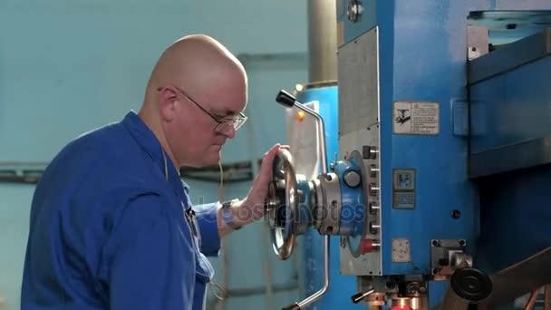 Zaměstnanci továrny otáčení páky na obráběcí stroj pro zpracování částí