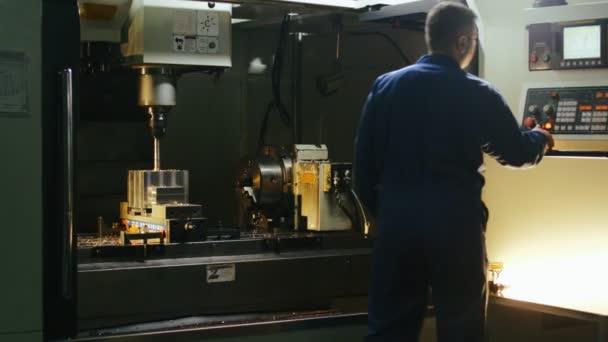 Tovární dělník pomocí moderní počítačové vybavení pro kontrolu kovoobráběcí stroje