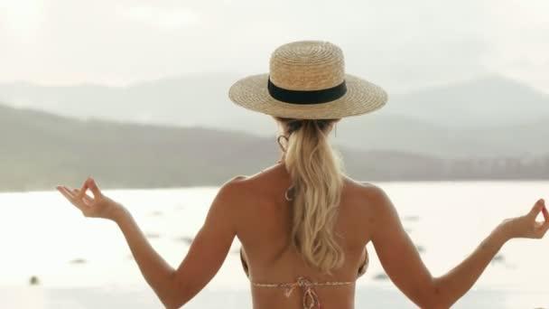 Relaxační žena sedí v lotosu představují na pozadí přírody moře a jóga