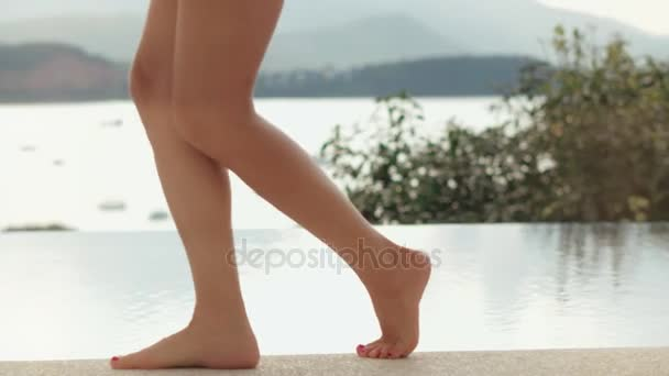 Female feet walking on edge infinity pool and putting cocktail glass on poolside