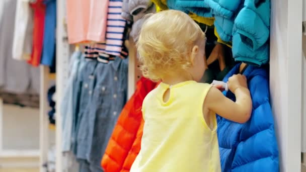Little girl touching clothes in childrens clothing store during family shopping