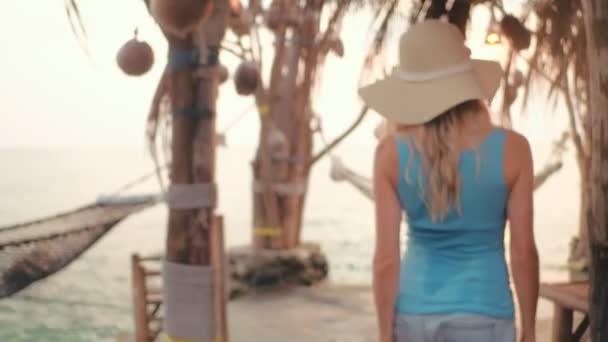 Krásná žena v klobouku beach leží v houpací síti beach na letní prázdniny