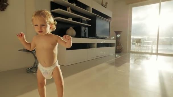 Malá holčička učení chůze na prostorný pokoj v moderních apartmánech