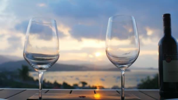 Két pohár és borosüveg állva a táblázat a háttér sunset égen