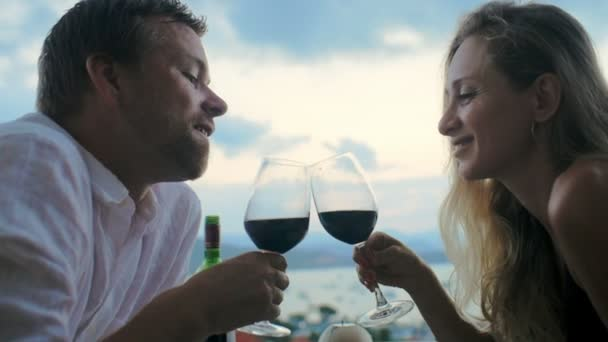Loving couple talking face to face and drinking red wine from glass on dinner