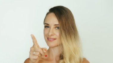 Smiling woman pointing with finger up and winking eye on white background
