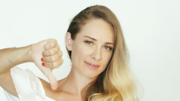 Atraktivní žena ukazuje ruku gestem palec dolů na bílém pozadí