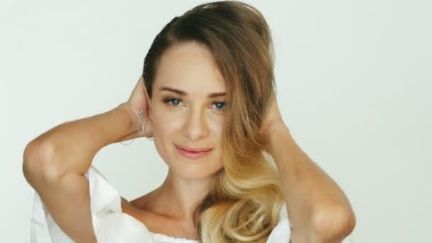 Gyönyörű nő megérintette a kötet frizura, és pózol a kamera elé