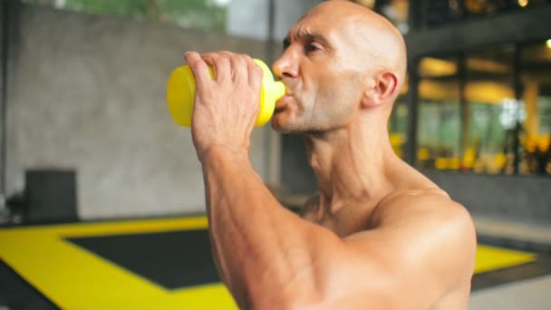 Tired athlete man drinking water from sport shaker after fitness training