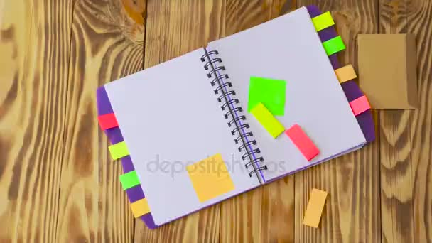 Marker esik le a táblázat / fa háttér. Nyit jegyzék és irodaszerek. Nyílt Jegyzettömb fekszik egy fából készült asztal marker, ceruza, toll és matricák
