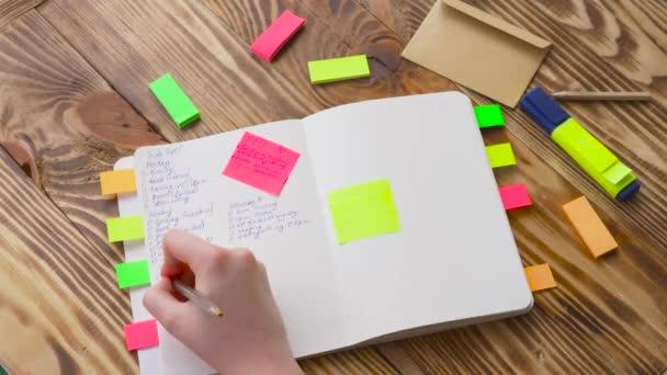 Nő jegyzeteket írni a Jegyzettömb. Nyit jegyzék és irodaszerek. Nyílt Jegyzettömb fekszik egy fából készült asztal marker, ceruza, toll és matricák