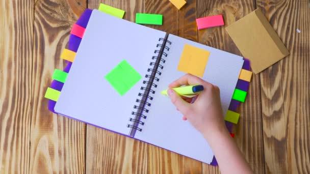 Žena se otevře Poznámkový blok a kreslí úsměv. Spusťte program Poznámkový blok s kancelářské potřeby. Spusťte program Poznámkový blok leží na dřevěné ploše s značek, tužka, pero a samolepky