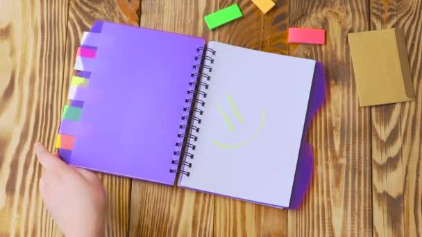 Nő megnyílik a Jegyzettömb, és felhívja a mosoly. Nyit jegyzék és irodaszerek. Nyílt Jegyzettömb fekszik egy fából készült asztal marker, ceruza, toll és matricák