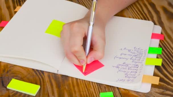 Žena psát poznámky v programu Poznámkový blok. Spusťte program Poznámkový blok s kancelářské potřeby. Spusťte program Poznámkový blok leží na dřevěné ploše s značek, tužka, pero a samolepky