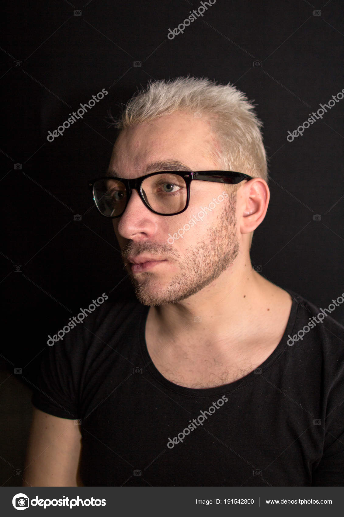 811e567c4885 A portrait of a young bearded man. A guy looking away. Man in black t-shirt  and eye glasses on black background.– stock image