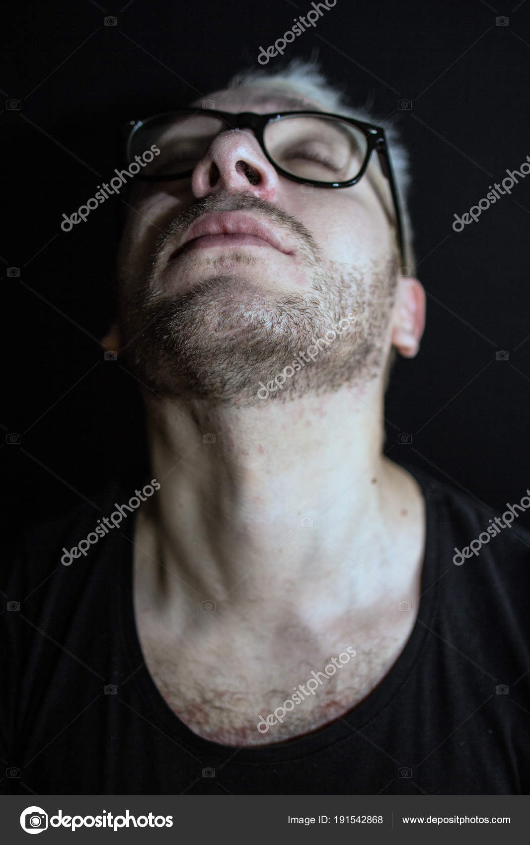 5052202bb4a7 A portrait of a man with black glasses. A man with closed eyes. portrait of a  man with a raised head on a black background.– stock image