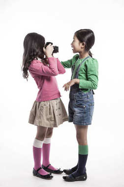 Two asian girls take pictures and play.