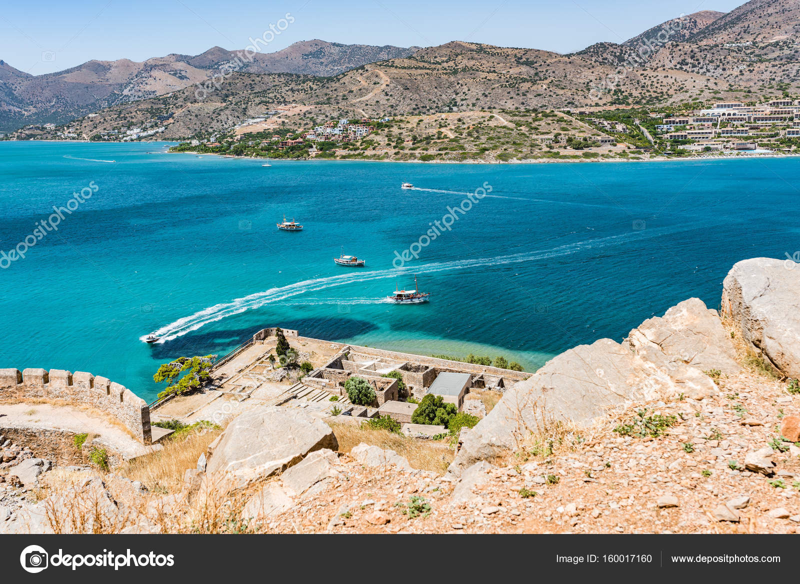 Top of Spinalonga fortress. View to blue aegian sea with boats, and Mirabello coast.