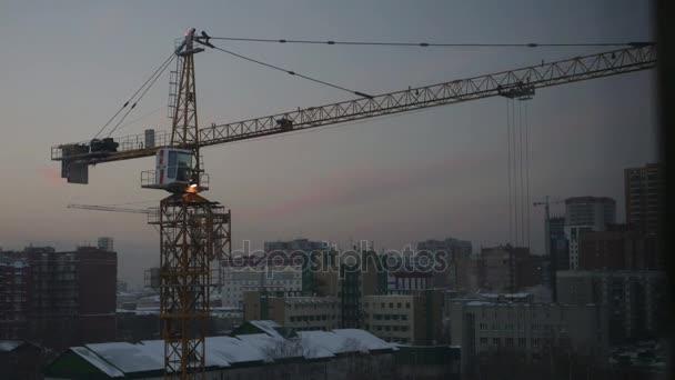 dělníci na staveništi shromažďovat stavební jeřáb při západu slunce, Timelapse