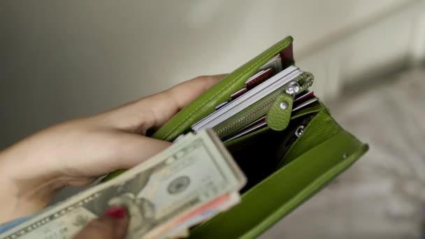 girl with beautiful monikyurom puts money Dolar, rupees, baht, rubles into empty green kashelek credit card, 4k., 3840x2160