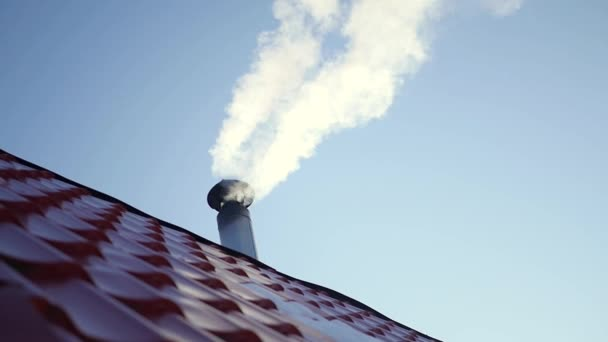 Beautiful white smoke from the chimney of house with red roof tiles, on a background of pure bright blue sky, slow motion. 1920x1080.