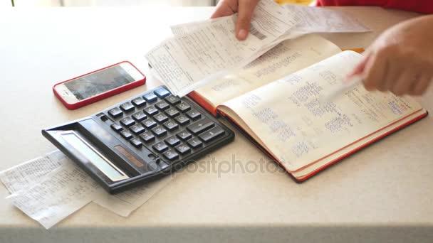 der Buchhalter legt die Schecks auf den Tisch neben dem Taschenrechner und dem Telefon. 4k