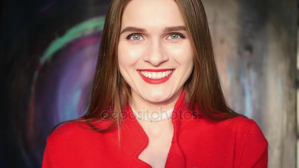 Zpomalený pohyb. Usmívající se krásná mladá dívka s červenou rtěnku, portrét.