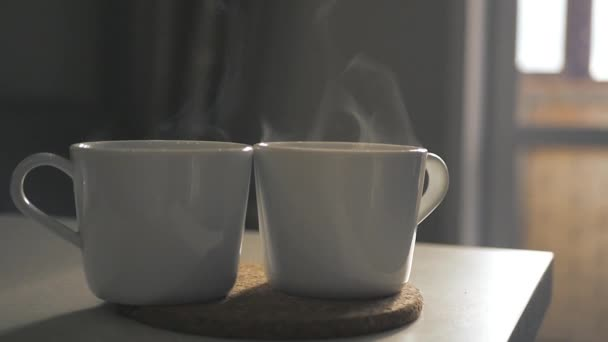 Two white cups of hot tea stand on the table, with a beautiful curly steam. Slow motion. 1920x1080.