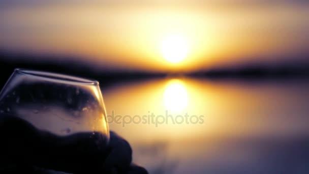 Dvě sklenice na pozadí krásný západ slunce s lahodné nápoje. Zpomalený pohyb. 1920 × 1080. full hd