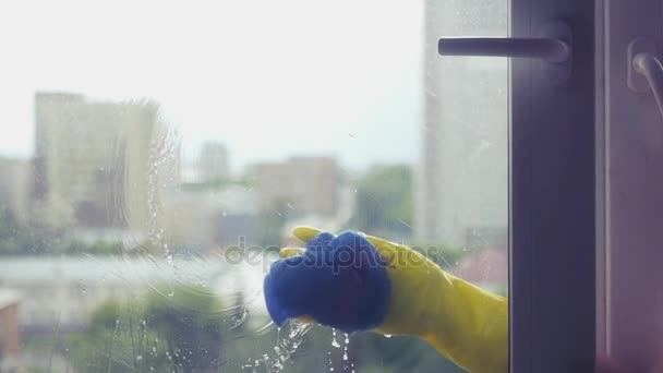 Wash the dirty window in yellow gloves with a blue rag. SLOW MOTION. HD, 1920x1080.