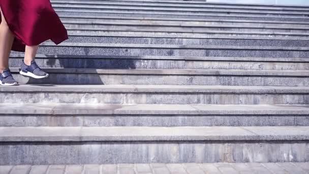 Dívka v tenisky a oblečení jde po kamenných schodech dolů. HD, 1920 × 1080. Zpomalený pohyb