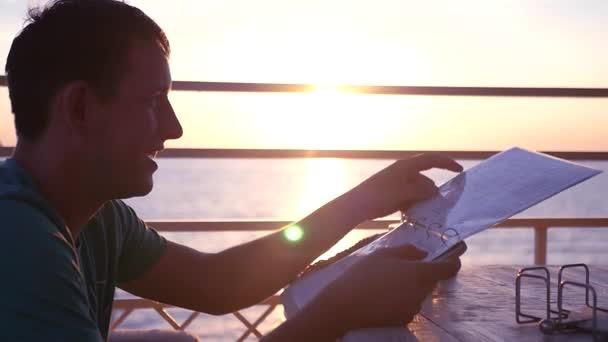 Ein junger Mann in eine gute Stimmung, sitzen in einem Café am Strand bei einem Sonnenuntergang, scrollt durch das Menü, eine Wahl zu treffen will. HD, 1920 x 1080. Slow-motion