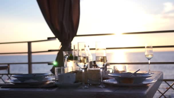 In a cafe at sunset by the sea, cover a table with plates and glasses. HD, 1920x1080. slow motion