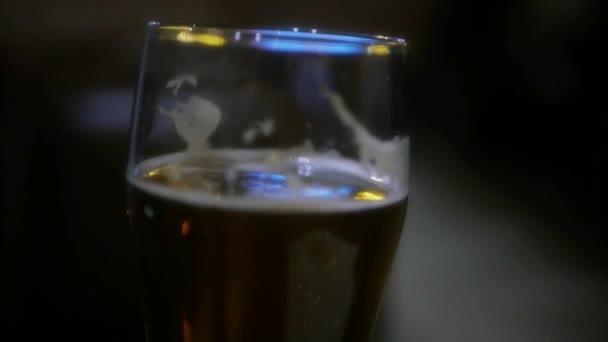 Sklo s šumivé čerstvé pivo. HD, 1920 × 1080. Zpomalený pohyb.