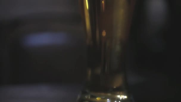 Sklenicí točeného piva stojí na stole v baru s krásnou rozostřeného pozadí. slowmotion, Hd, 1920 x 1080