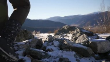 A woman in winter boots rises over rocks in the snow. slow motion, 1920x1080, full hd