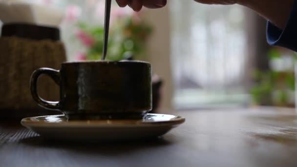 Keverje hozzá a forró teát vagy kávét egy pohár, egy kanál fektetni a csészealj. lassú mozgás, 1920 x 1080 full hd