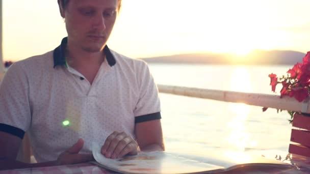 Muž sedí v kavárně u moře s výhledem na krásný západ slunce, se dívá na v nabídce, je výběr. HD, 1920 × 1080. Zpomalený pohyb.