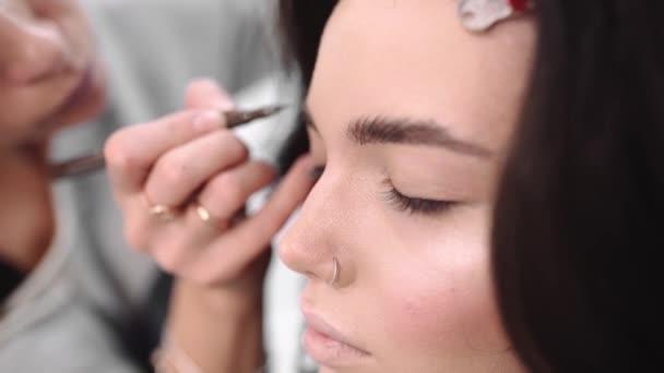 Make-upu umělec maluje obočí tužkou, tvoří umělec tvoří model, Žena v salonu krásy, fotografie modelu dostane připraven k focení