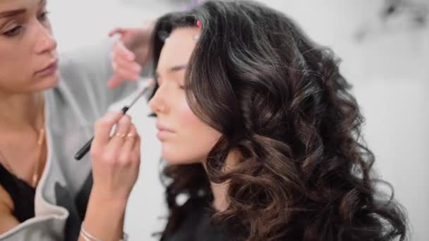 Make up stylist makes smokey eyes effect for woman at photo shoot, make up for beautiful caucasian model, girl comes to beauty salon, sexy cutie with long brown hair