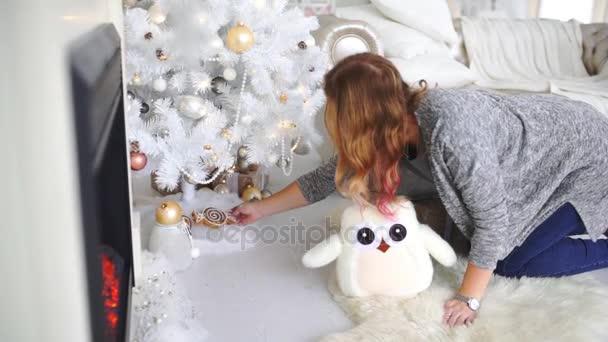 Žena dává dárky pod vánoční stromeček, dárky pod vánoční stromeček, přípravy před novým rokem, Zimní dovolená
