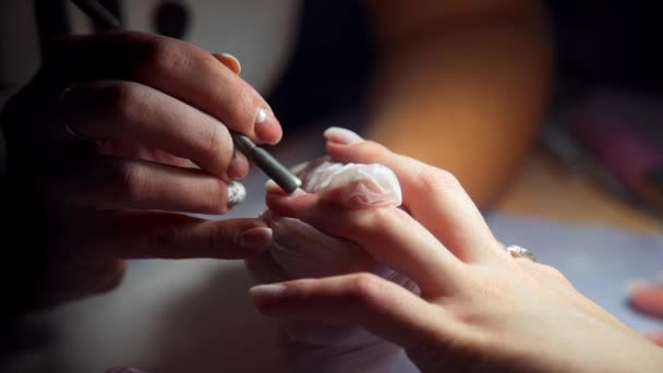 Manikérka je lemování manikúra, Žena přijde do salonu manikúra, péče o nehty, podnikání v kráse