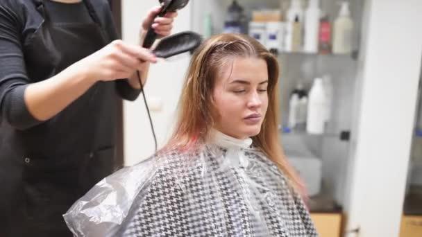Kadeřník schne ženách vlasy po umytí, žena dělá nový účes v studio krásy, zdraví a kosmetika