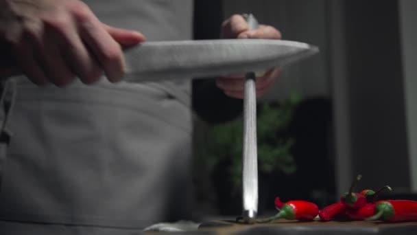 Kuchař brousí nože v kuchyni, přípravy na vaření potravin, kuchyňské náčiní, vaření potravin, chutné recepty, jídlo videa